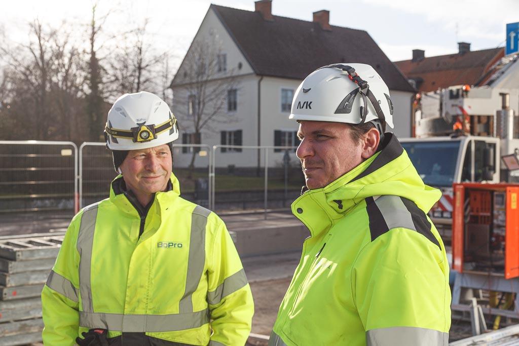 Arbetsledare på byggarbetsplats ser över pågående arbete